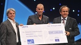 ELA President Guy Alba and ELA ambassador Zinédine Zidane accept a cheque for CHF1m from UEFA President Michel Platini during the UEFA Champions League draw in Monaco