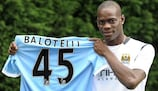 Mario Balotelli shows off the colours of his new club after being unveiled as a Manchester City player