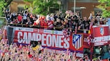 Atlético's open-top bus snakes its way through the throng of jubilant fans