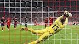 Goalkeeper Jan Oblak dives to save Thomas Müller's penalty