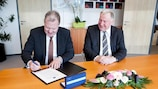 UEFA first vice-president Karl-Erik Nilsson signs the #CohesionAlliance declaration, watched by the president of the European Committee of the Regions, Karl-Heinz Lambertz