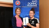 Caroline Thom, da UEFA, entrega o prémio à alemã Katja Friedl depois de esta ter vencido o questionário antidoping