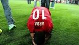 Turkey midfielder Arda Turan kneels on the pitch, overcome by disbelief