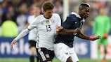 Germany forward Thomas Müller and France midfielder Paul Pogba vie for possession