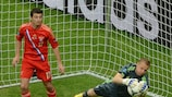 Vyacheslav Malafeev makes a save during Russia's draw with Poland as scorer Alan Dzagoev looks on